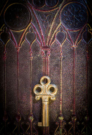 Old golden metal key lying on a decorated ancient book cover photo