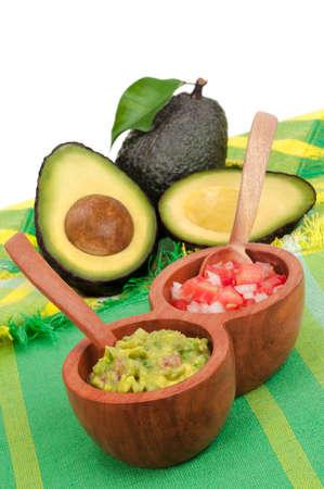 Verse guacamole en pico de gallo met avocado's in de achtergrond