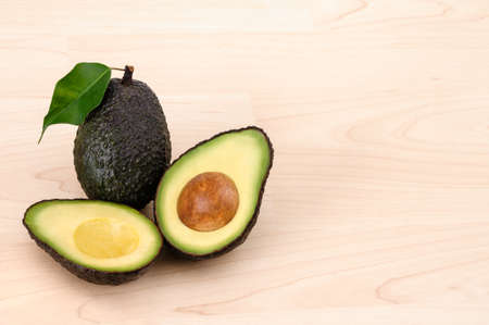Fresh Avocados one halved over a wood background with copy space photo