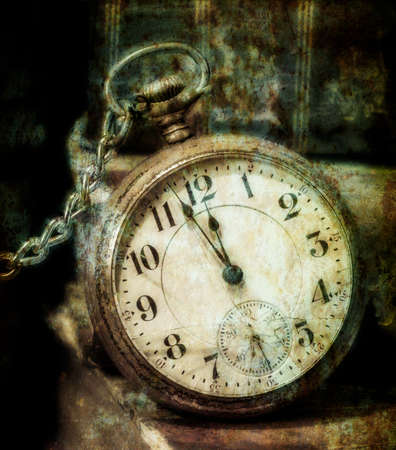 Antique pocket clock showing a few minutes to midnight grungy style  Concept of time,the past  photo