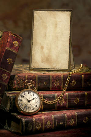 Vintage wood desk with Antique Frame with old photo paper texture, Books and Old Pocket Clock in Low-key  Stock Photo - 16461805