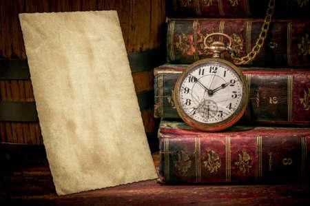 Vintage houten bureau met oude foto textuur, boeken en oude zak klok in low-key concept van de tijd, het verleden of de termijn