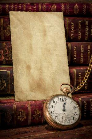 reloj antiguo: Escritorio de madera de la vendimia con la textura de papel viejo de fotos, libros y reloj de bolsillo antiguo mostrando unos minutos para la medianoche en Low-clave concepto del tiempo, más allá de la fecha límite o