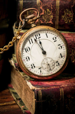 Antique pocket clock showing a few minutes to midnight over ancient books in Low-key  Concept of time,the past or deadline  Stock Photo
