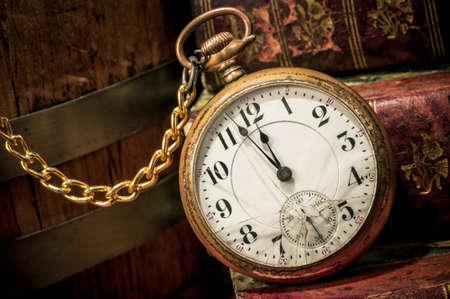 Antico orologio da tasca che mostra pochi minuti a mezzanotte sui libri antichi in Low-chiave Concetto di tempo, il passato o il termine Archivio Fotografico - 16461806