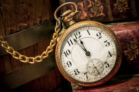 pocketwatch: Antique pocket clock showing a few minutes to midnight over ancient books in Low-key  Concept of time,the past or deadline  Stock Photo