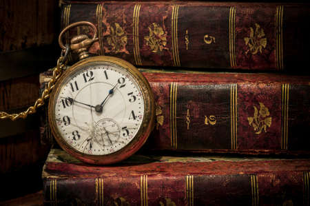 Antique pocket clock over ancient books in Low-key, copy space  Concept of time,the past or deadline  photo