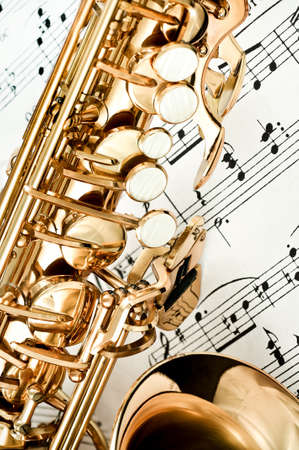 brass band: Saxophone keys closeup with score notes in background Stock Photo