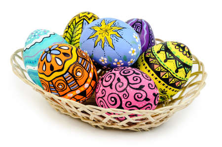Easter eggs in basket isolated on white background photo