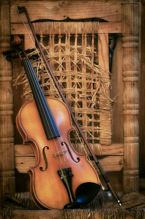 Left handled Violin lying on an old and ruined chair Standard-Bild