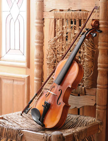 Violin lying on an old and ruined chair under window light Stock Photo