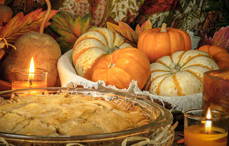 Pumpkins and cake on candle light still life Stock Photo