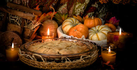 Pumpkins and cake on candle light still life photo