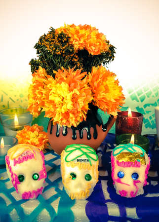 Traditional Mexican Day of the dead altar with sugar skulls flowers and candles photo