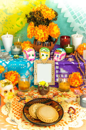 Traditional mexican day of the dead altar with blank photo frame, sugar skulls, cempasuchil flowers, candles and cookies