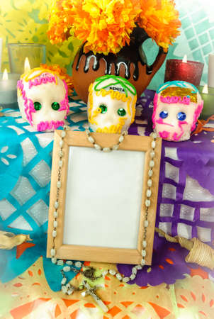 Traditional mexican day of the dead altar with blank photo frame, sugar skulls and candles