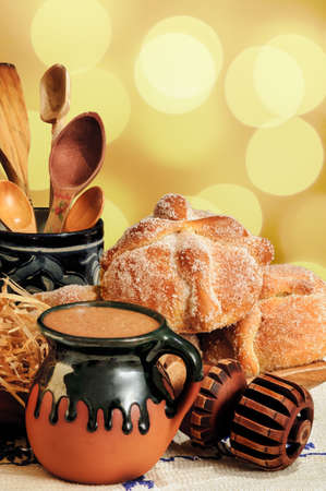 Jar of hot chocolate and sweet bread (pan de muerto) with wooden chocolate grinder and spoons on festive background
