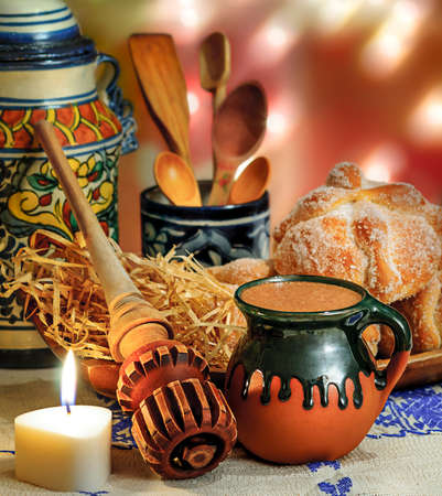 Jar of hot chocolate and sweet bread (pan de muerto) with wooden chocolate grinder and spoons on festive background photo