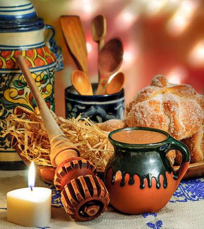 Jar van warme chocolademelk en zoet brood (pan de muerto) met houten chocolade molen en lepels op feestelijke achtergrond