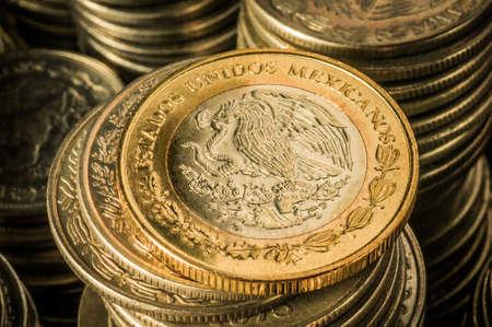 mucho dinero: Una moneda de oro con un �guila sobre pilas de la riqueza empresarial monedas de plata y el concepto de �xito