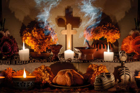 Traditional mexican Day of the dead altar with pan de muerto and candles