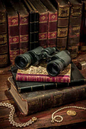 opportunity discovery: Binoculars and old books over wooden desk
