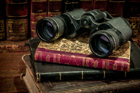 old books: Binoculars and old books over wooden desk