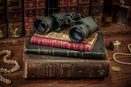 old desk: Binoculars and old books over wooden desk