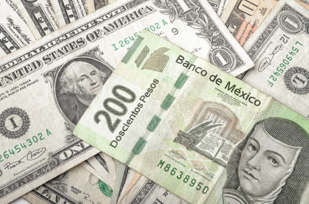 pesos: Dollars and Mexican Pesos assorted bills cash pile background Stock Photo