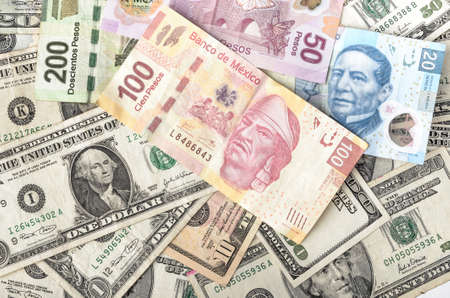 heap of dollar: Dollars and Mexican Pesos assorted bills cash pile background Stock Photo