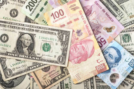 currencies: Dollars and Mexican Pesos assorted bills cash pile background Stock Photo