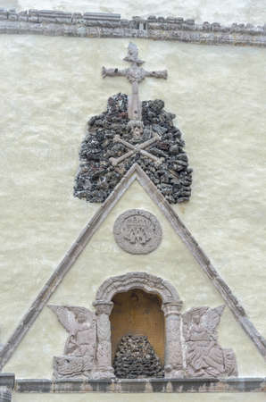 Skull on a pile of stones on which rests a cross. This symbol is located on the side door of the Cathedral of Cuernavaca, represents the Golgotha (Calvary Hill) where Jesus was crucified, the same site where the remains of Adam are buried represented here