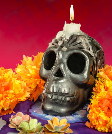 Day of the dead Oaxacan black clay Skull with candle Stock Photo