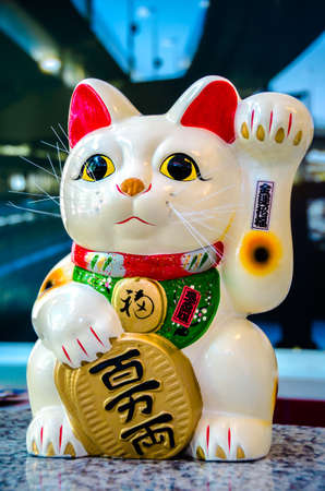 maneki neko: Lucky Cat, Maneki Neko or Zhaocai Mao, ancient cultural icon from japan and popular in many asian cultures. Stock Photo