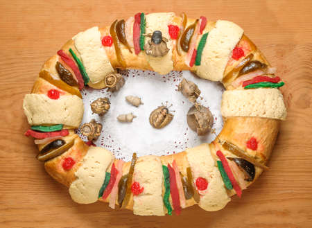 Epiphany Cake, kings cake, or Rosca de reyes with manger on wooden table