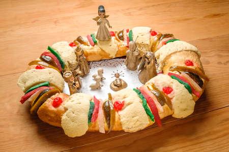 portal de belen: Roscón de reyes, reyes de la torta o rosca de reyes con pesebre en mesa de madera Foto de archivo