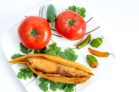Tamales, Mexican dish made with corn dough, chicken and chili, wrapped with a corn leaf  isolated on white Stock Photo