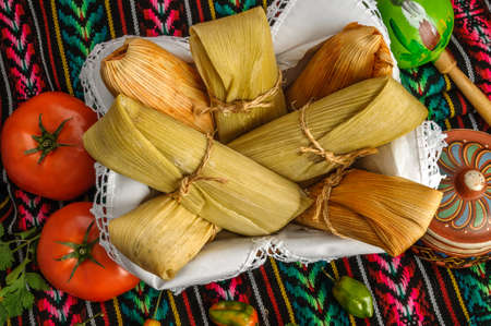 husk tomato: Tamales, Mexican dish made with corn dough, chicken and chili, wrapped with a corn leaf Stock Photo