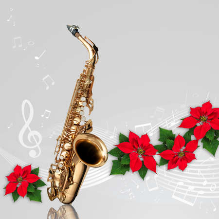 Saxophone with musical notes and Red Poinsettia flower Christmas ornament on gray background