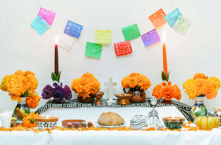 Traditional mexican Day of the dead altar with pan de muerto and candles over white background