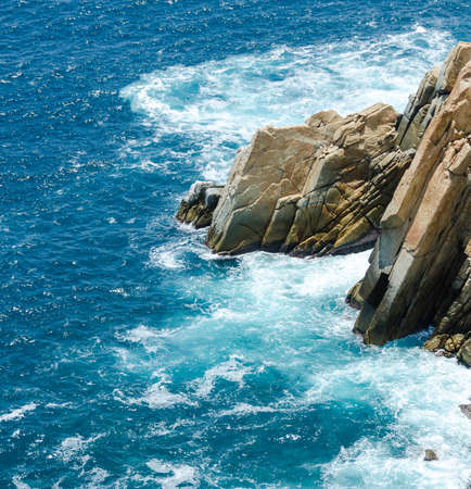 Blue sea with rocky shore in sunny afternoon, Acapulco, Mexico.