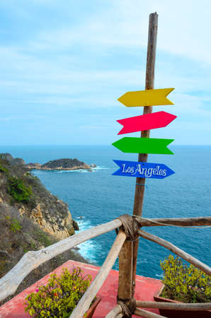 Signpost with directions at tropical vacation bar lounge on a cliff with blue sea in Acapulco, Mexico.