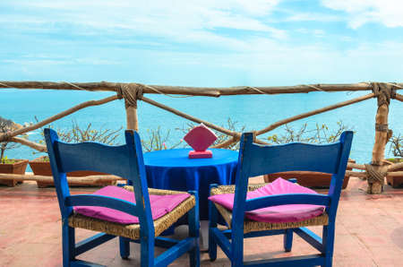 Coffee table on rustic balcony, with cliff and blue sea in background in Acapulco, Mexico. Stok Fotoğraf