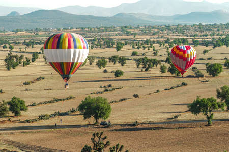 Colorful hot air balloons landing in rural farm fields