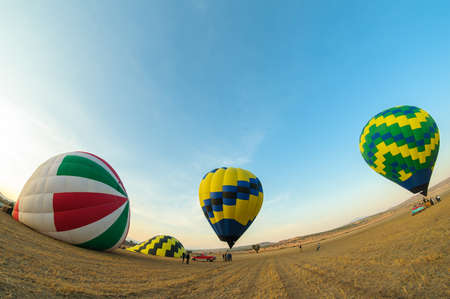 Teotihuacan, Mexico - April 6, 2019 : Colorful hot air balloons about to take off at dawn in rural field with blue sky near the town of Teotihuacan, Mexico.