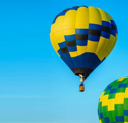Colorido globo de aire caliente despegando con cielo azul y espacio de copia Foto de archivo