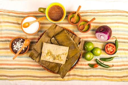 Tamales Oaxaqueños, platillo mexicano elaborado con masa de maíz, pollo o cerdo y ají, envuelto en hojas de plátano.