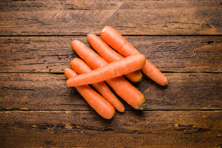 Top view fresh organic carrots on wooden table top