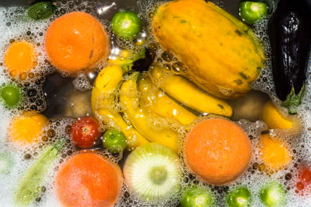 Fruit and vegetables washing in soapy water for coronavirus disinfection. Фото со стока