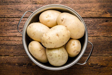Top view fresh organic potatoes on wooden table top Imagens